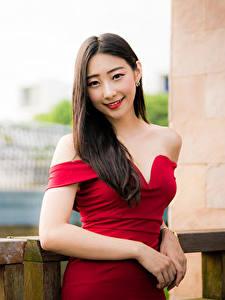 Bilder Asiatische Kleid Lächeln Hand Blick Unscharfer Hintergrund junge Frauen