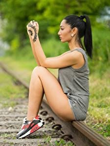 Fotos Unscharfer Hintergrund Schienen Sitzt Hand Tätowierung Bein Brünette Mädchens