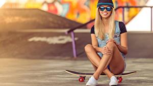 Bilder Skateboard Blond Mädchen Lächeln Brille Baseballmütze Sitzend Bein Mädchens