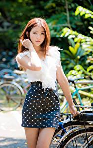 Fotos Asiaten Unscharfer Hintergrund Rock Bluse Hand Braune Haare Starren junge frau