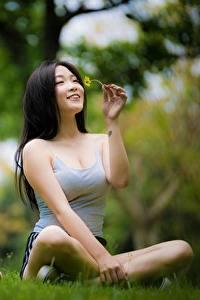 Bilder Asiaten Lotossitz Brünette Bokeh Sitzen Lächeln Hand Gras Freude Mädchens