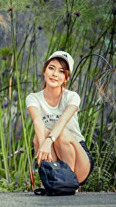 Hintergrundbilder Asiatisches Handtasche Sitzen T-Shirt Baseballmütze Lächeln Starren Mädchens