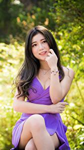 Fotos Asiatische Brünette Sitzen Kleid Bein Starren Bokeh junge frau