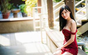 Fotos Asiaten Unscharfer Hintergrund Sitzt Kleid Brünette Starren junge frau