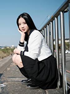 Fotos Asiatische Brünette Pose Sitzend Uniform Schulmädchen Blick junge frau