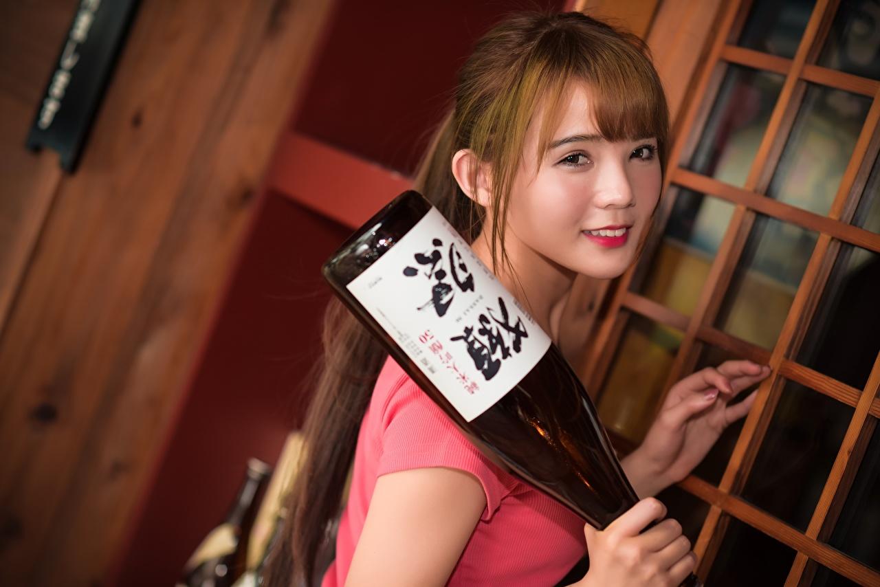 Desktop Hintergrundbilder Braune Haare Lächeln Mädchens Asiaten flaschen Starren Braunhaarige junge frau junge Frauen Asiatische asiatisches Flasche Blick