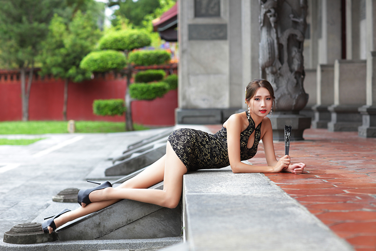 Image esting blurred background young woman Legs Asian Glance frock laying Lying down Bokeh Girls female Asiatic Staring gown Dress