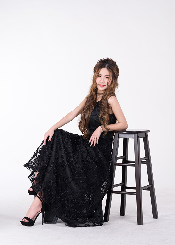 Photos Black Girls Asiatic sit Chairs Staring Gray background Dress  for Mobile phone female young woman Asian Chair Sitting Glance gown frock