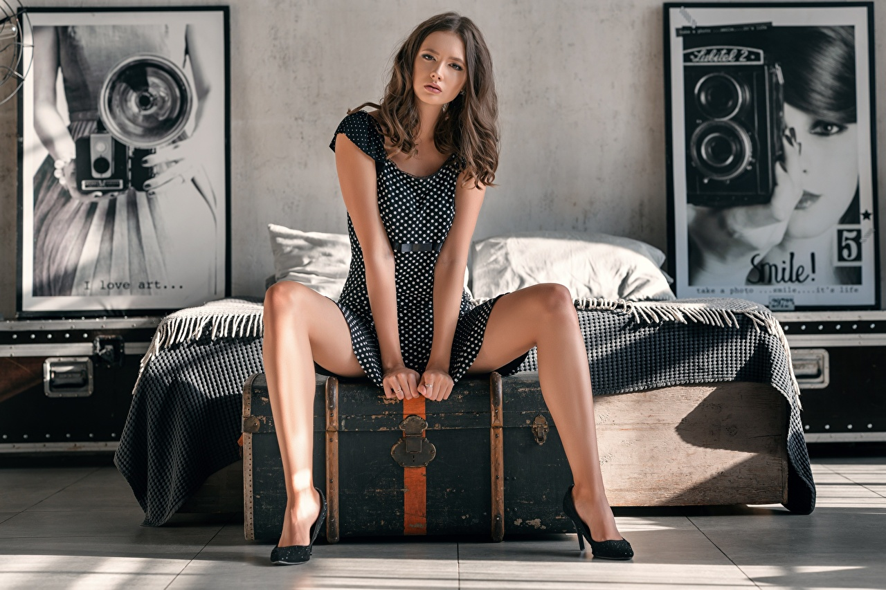Bilder Braunhaarige Disha Shemetova, Sergey Vasiliev posiert Mädchens Bein Hand Bett sitzt Kleid Braune Haare Pose junge frau junge Frauen sitzen Sitzend