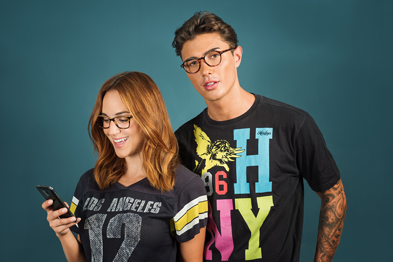 Image Smile guys Smartphone 2 T-shirt young woman Glasses Glance guy Young man teenage guy smartphones Two Girls female eyeglasses Staring