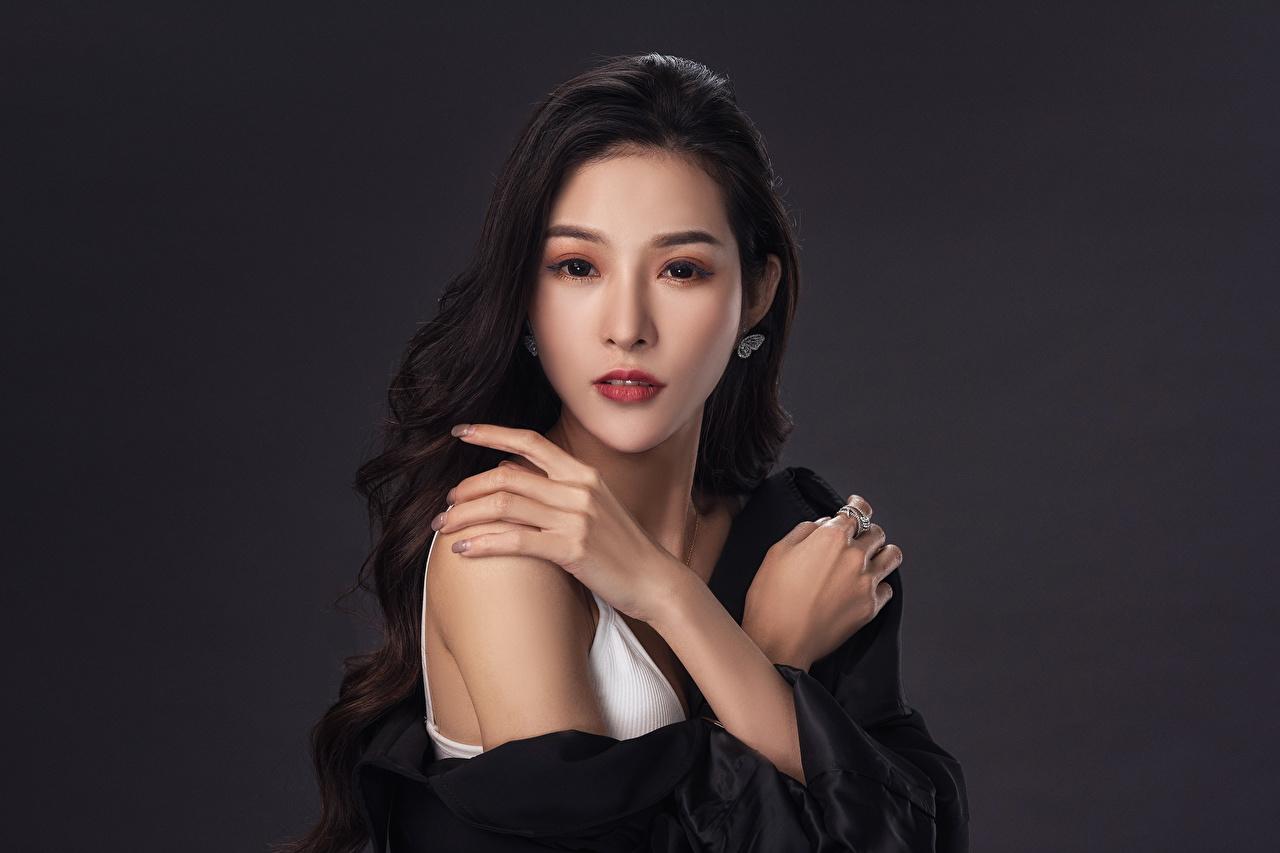 Fotos von Brünette junge Frauen Asiatische Hand Starren Grauer Hintergrund Mädchens junge frau Asiaten asiatisches Blick