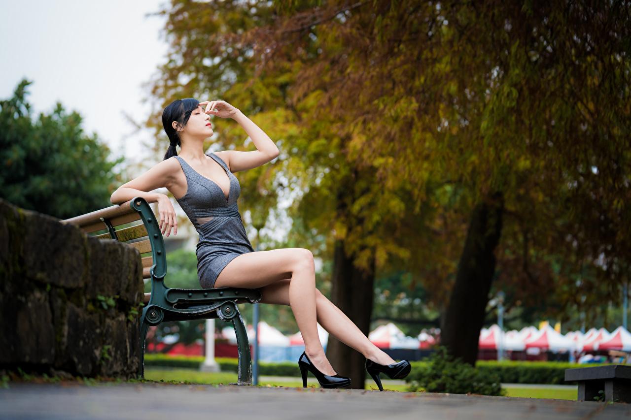 Bilder Brünette Bokeh junge Frauen Bein asiatisches Hand Sitzend Bank (Möbel) Kleid Stöckelschuh unscharfer Hintergrund Mädchens junge frau Asiaten Asiatische sitzt sitzen High Heels