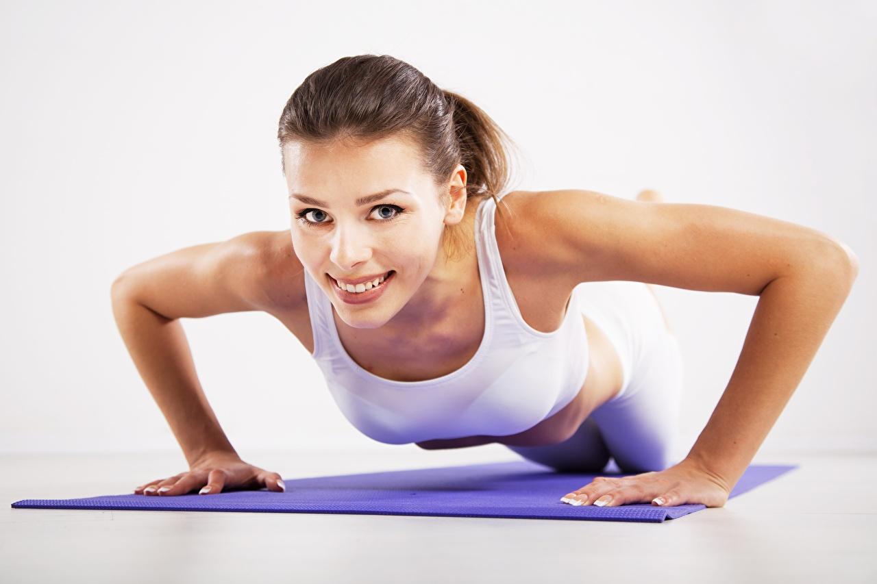 Bilder Liegestütz Braunhaarige Lächeln posiert Fitness Sport Mädchens Hand Starren Braune Haare Pose junge frau sportliches junge Frauen Blick
