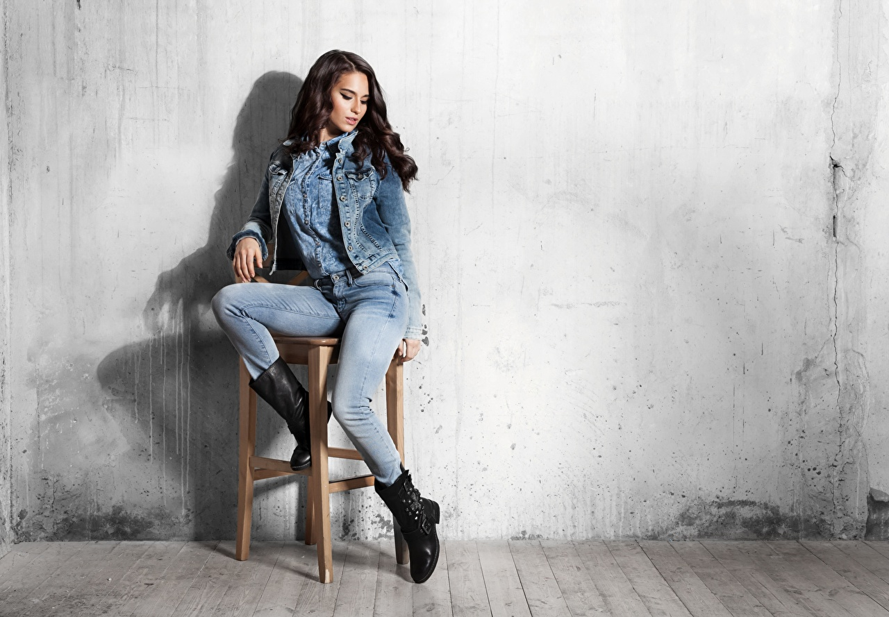 Photo Brunette girl Wearing boots Girls Legs Jeans sit Chair walls female young woman Wall Chairs Sitting
