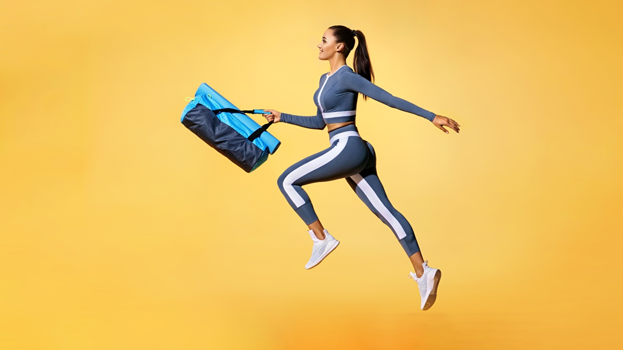 Photos Fitness Girls athletic Jump Handbag Colored background Sport female sports young woman purse