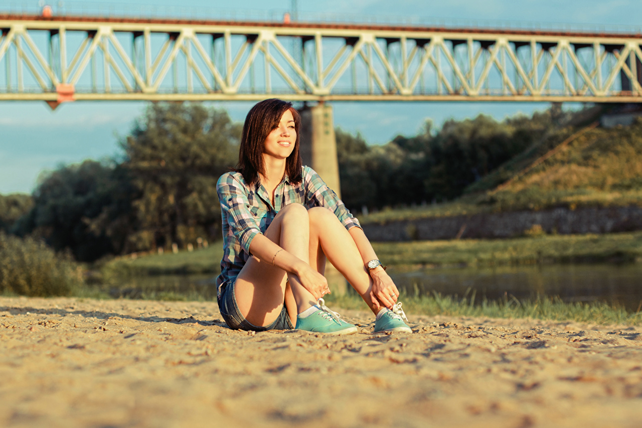 Photos Brown haired Smile blurred background Girls Sand Legs sit Hands Bokeh female young woman Sitting