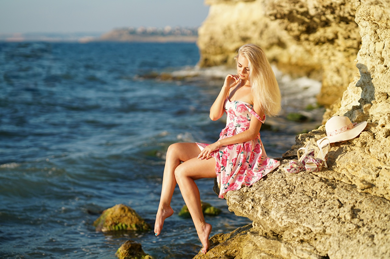 Photo Blonde girl Sea Hat Crag Girls Legs Sitting gown Rock Cliff female young woman sit frock Dress