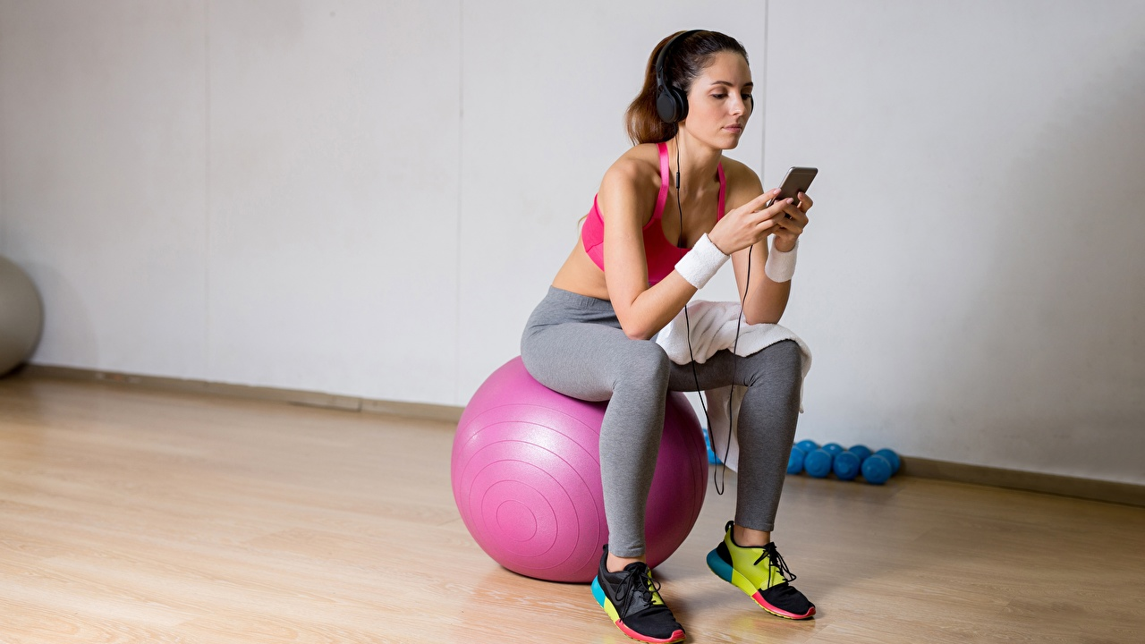 Photos Headphones Smartphone Fitness Girls trainers athletic Ball Sitting smartphones Sport sports female sneakers young woman Athletic shoe sit