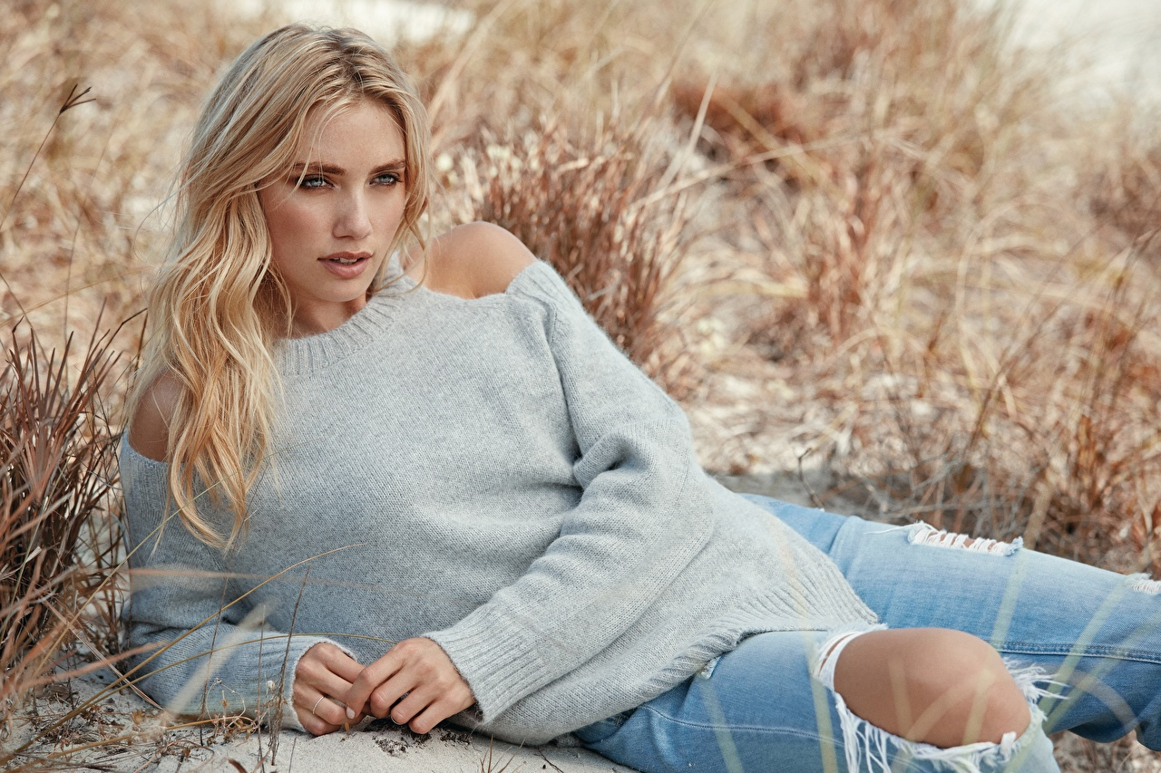 Image Blonde girl esting Bokeh female Jeans Sweater Grass Hands laying Lying down blurred background Girls young woman