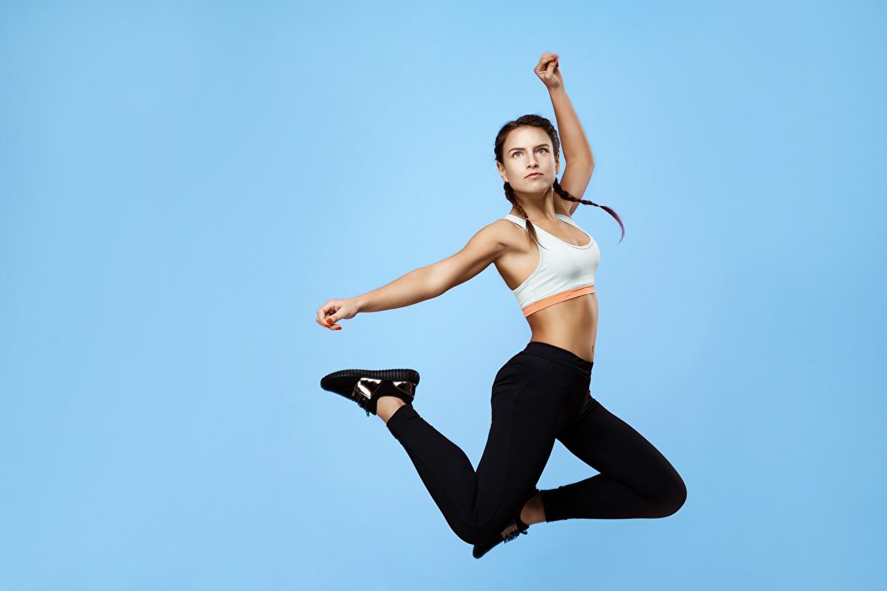 Skrivebordsbakgrunn Flette Fitness atletisk ung kvinne hoppende Farget bakgrunn Sport Unge kvinner hoppe Hoppere