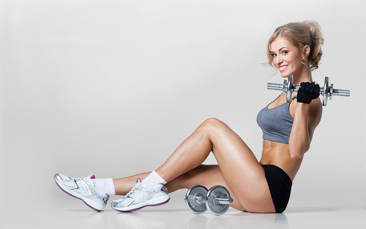 Bilder von Blondine Lächeln Fitness Hantel Turnschuh junge frau Bein Hand Sitzend Seitlich Grauer Hintergrund Blond Mädchen Hanteln Mädchens sportschuhe junge Frauen sitzt sitzen