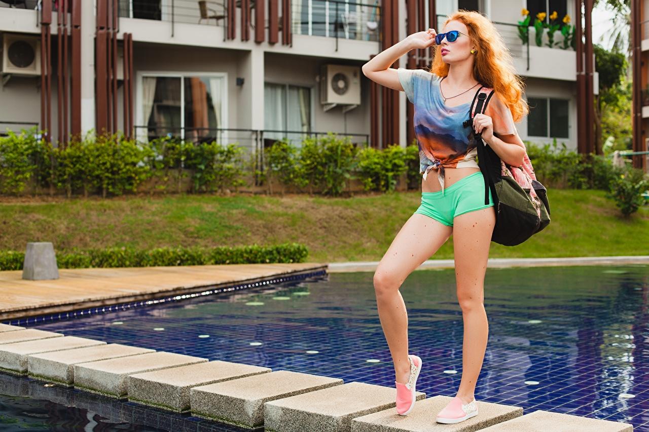Photo Redhead girl Pools Pose young woman Legs purse Shorts Glasses Staring Swimming bath posing Girls female Handbag eyeglasses Glance