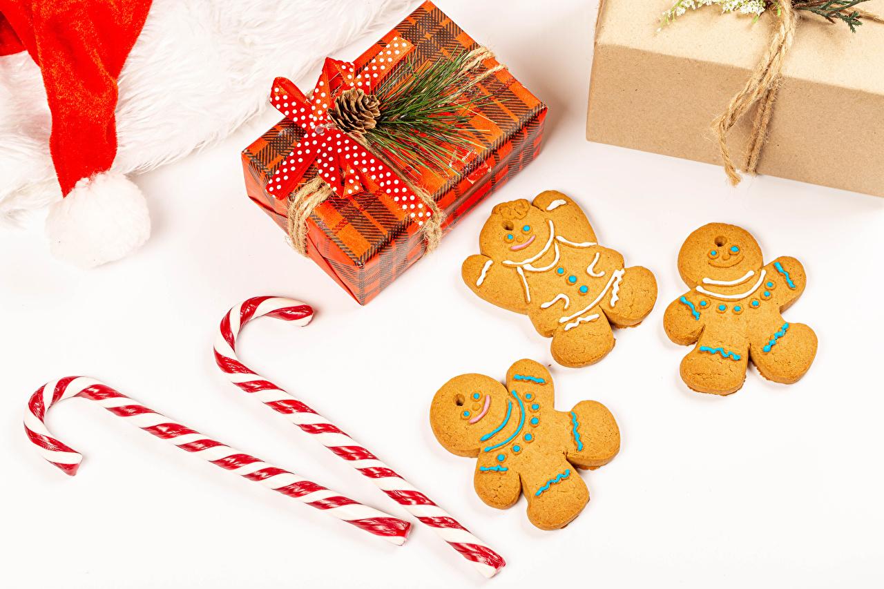 Fotos Neujahr Dauerlutscher Geschenke Kekse Zapfen Schleife Lebensmittel Weißer hintergrund das Essen