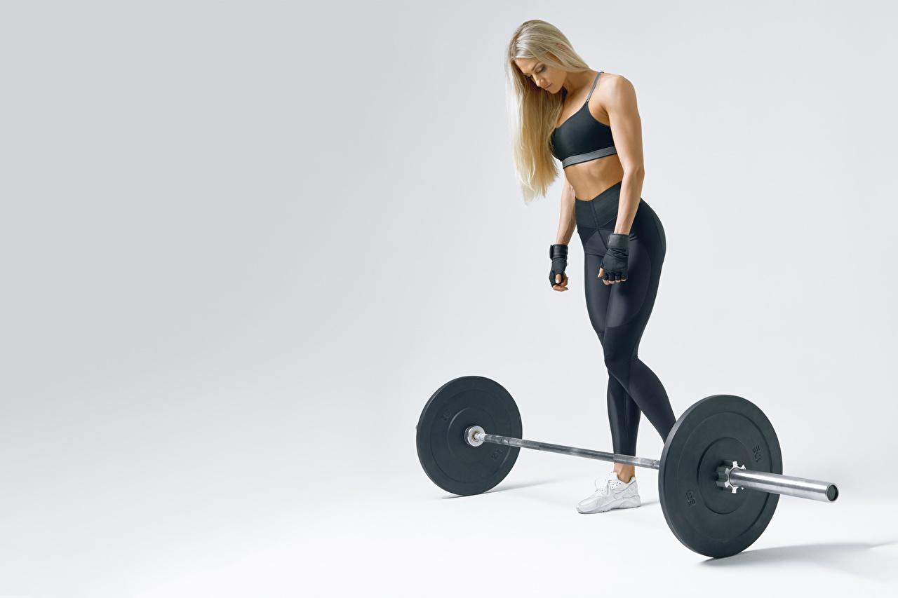 Fotos Blondine Fitness Sport Mädchens Hantelstange Grauer Hintergrund Blond Mädchen