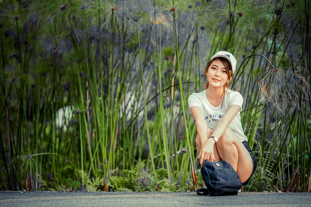 Fotos von Lächeln T-Shirt junge frau asiatisches sitzen Handtasche Blick baseballkappe Mädchens junge Frauen Asiaten Asiatische sitzt Sitzend Starren Baseballcap baseballmütze