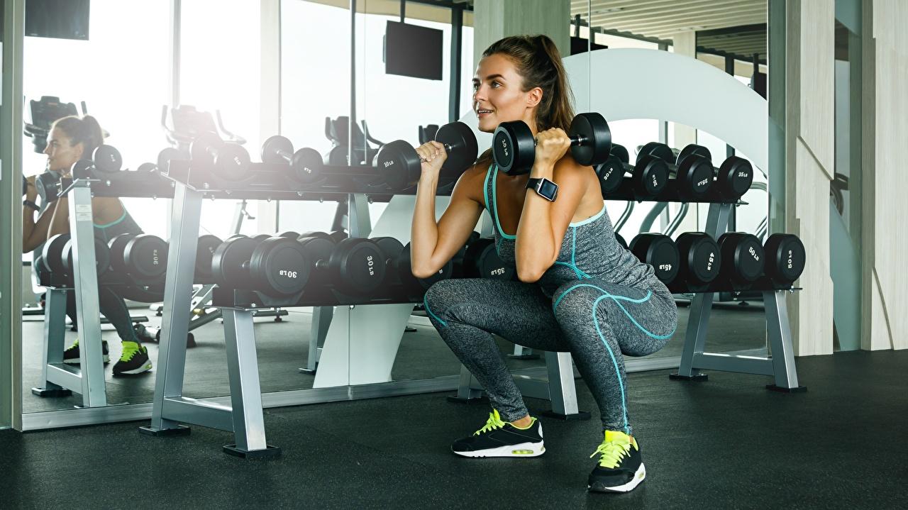 Fotos Turnhalle Körperliche Aktivität Kniebeugen Fitness Hanteln junge frau sportliches Trainieren Fitnessstudio hockt Kauert Sport Hantel Mädchens junge Frauen