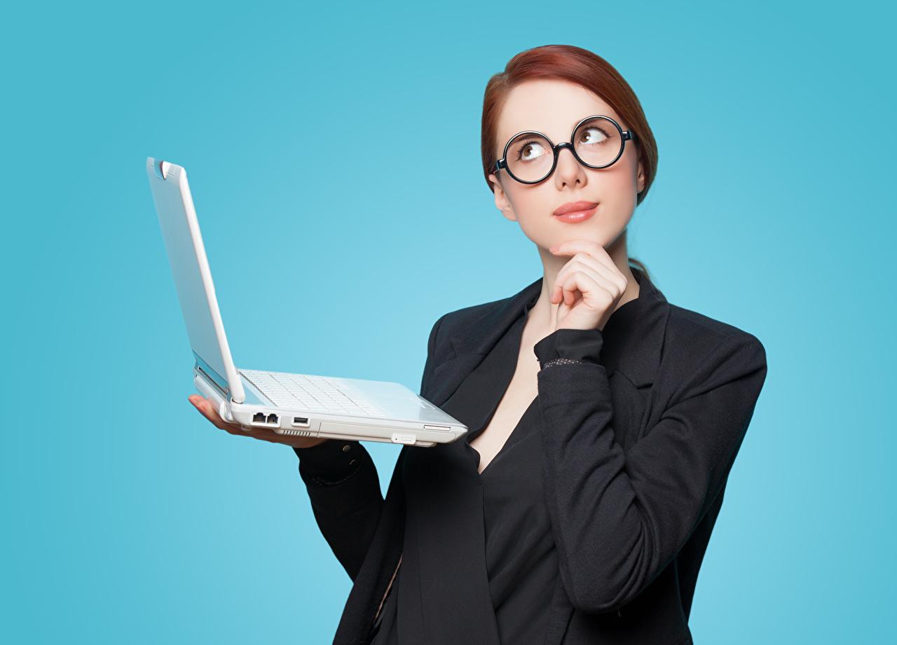 Bilder Bärbar dator Rödhårig tjej Unga kvinnor Glasögon ser Kavaj Färgad bakgrund ung kvinna Blick