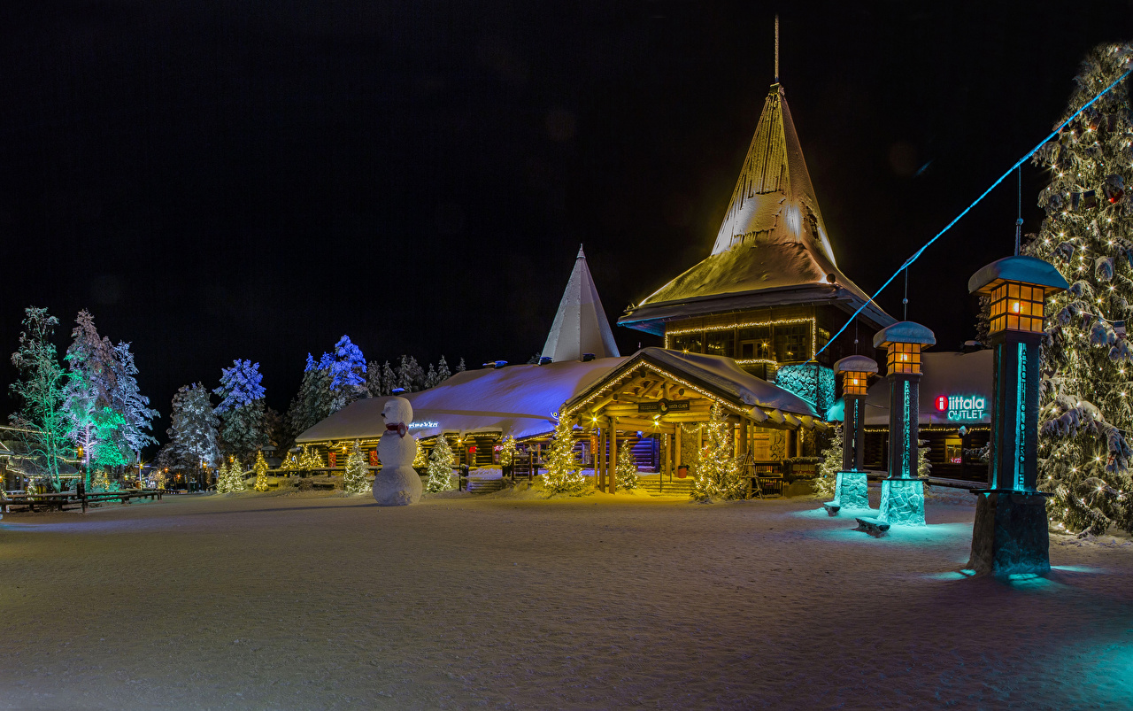 Picture Lapland region Finland Christmas Saariselka Winter Christmas tree Snow Snowman Night Fairy lights Street lights Houses Cities New year New Year tree Snowmen night time Building