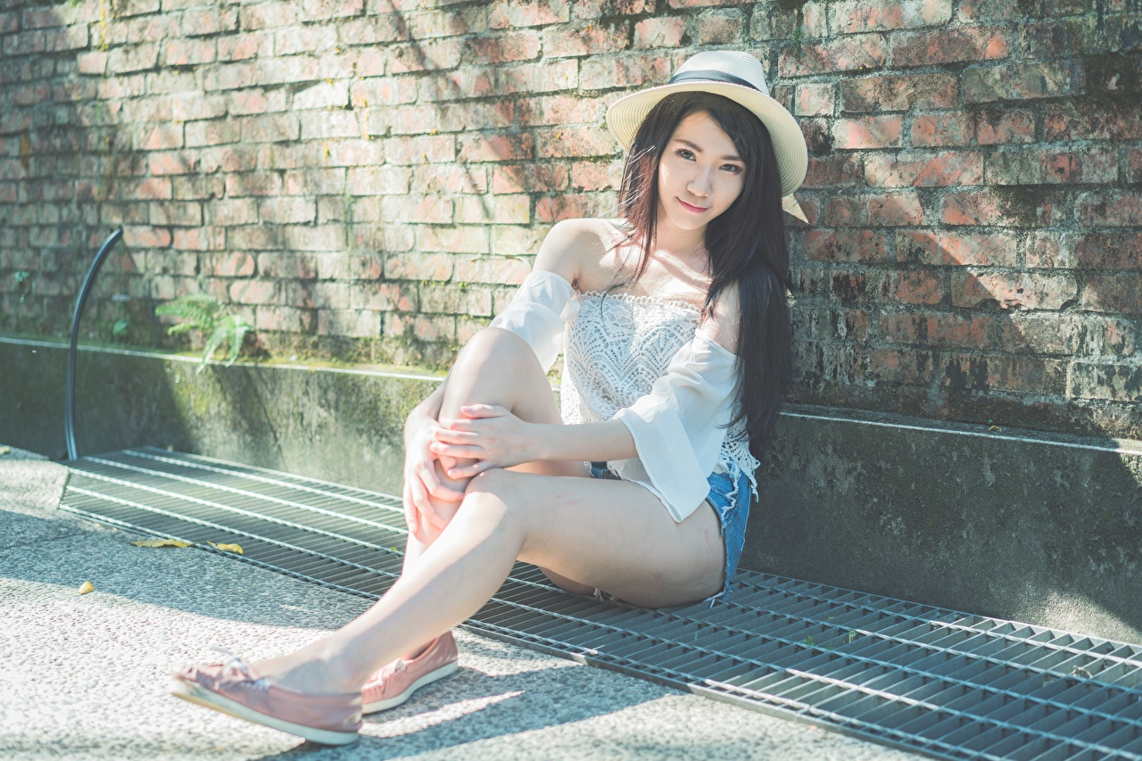 Picture Brunette girl Hat Girls Legs Asiatic sit Hands female young woman Asian Sitting