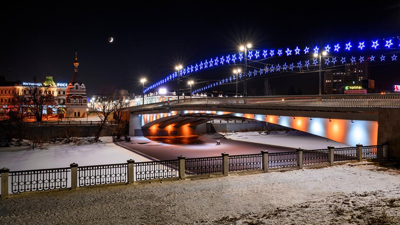 Picture Russia Omsk Bridge Jubilee Winter bridge river night time Fairy lights Street lights Houses Cities Bridges Night Rivers Building