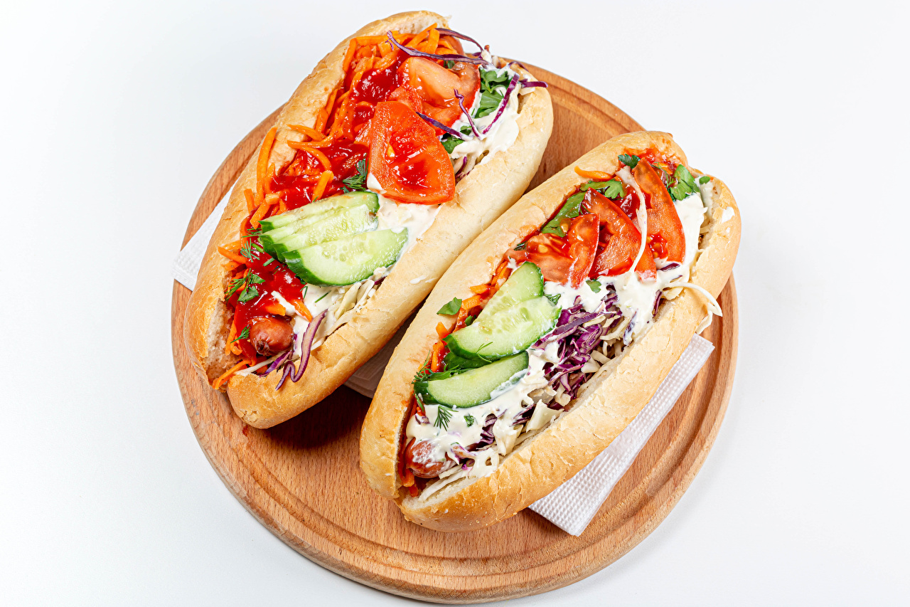Picture 2 Hot dog Tomatoes Cucumbers Buns Food Vegetables Cutting board White background Two