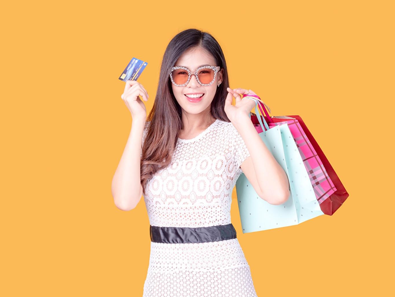 Fotos von Braunhaarige kaufte Tüte Lächeln junge Frauen Hand Brille Handtasche Farbigen hintergrund Braune Haare kaufen kauften Einkaufen Mädchens junge frau