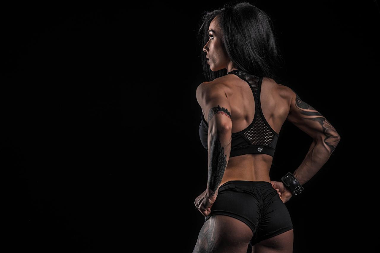 Foto Rumpa Tatuering Pose Rygg Fitness Sport Unga kvinnor Kortbyxor Bakifrån Svart bakgrund poserar atletisk ung kvinna