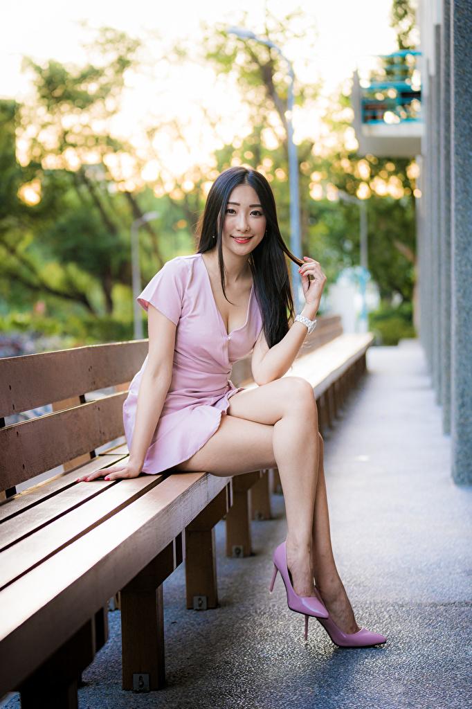 Desktop Hintergrundbilder Lächeln junge frau Bein asiatisches sitzen Bank (Möbel) Blick Kleid  für Handy Mädchens junge Frauen Asiaten Asiatische sitzt Sitzend Starren