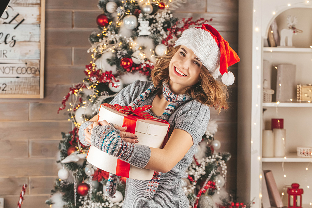 Images New year Brown haired Smile female Winter hat New Year tree Gifts Glance Christmas Girls young woman Christmas tree present Staring