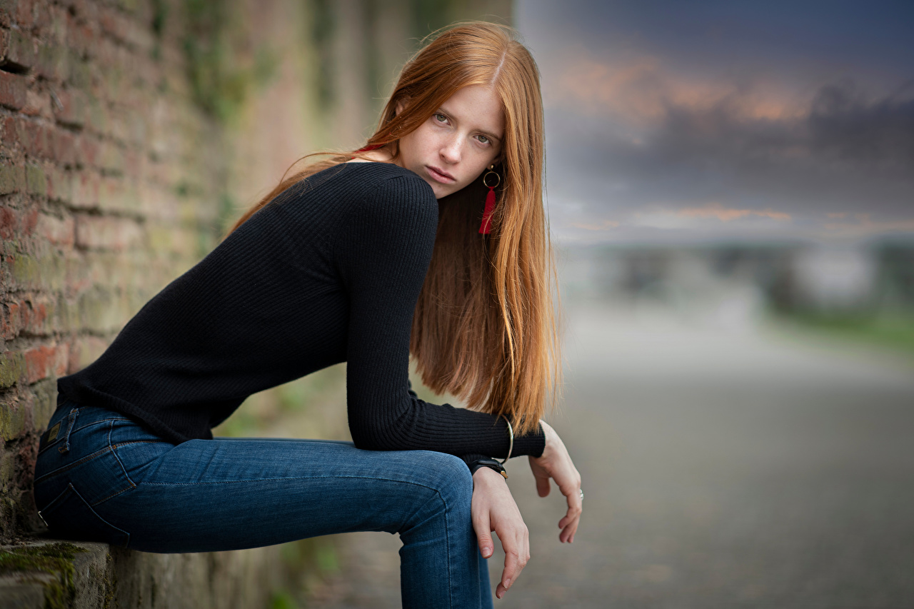 Image Redhead girl Modelling Bokeh Pose female Jeans Sweater sit Glance Model blurred background posing Girls young woman Sitting Staring