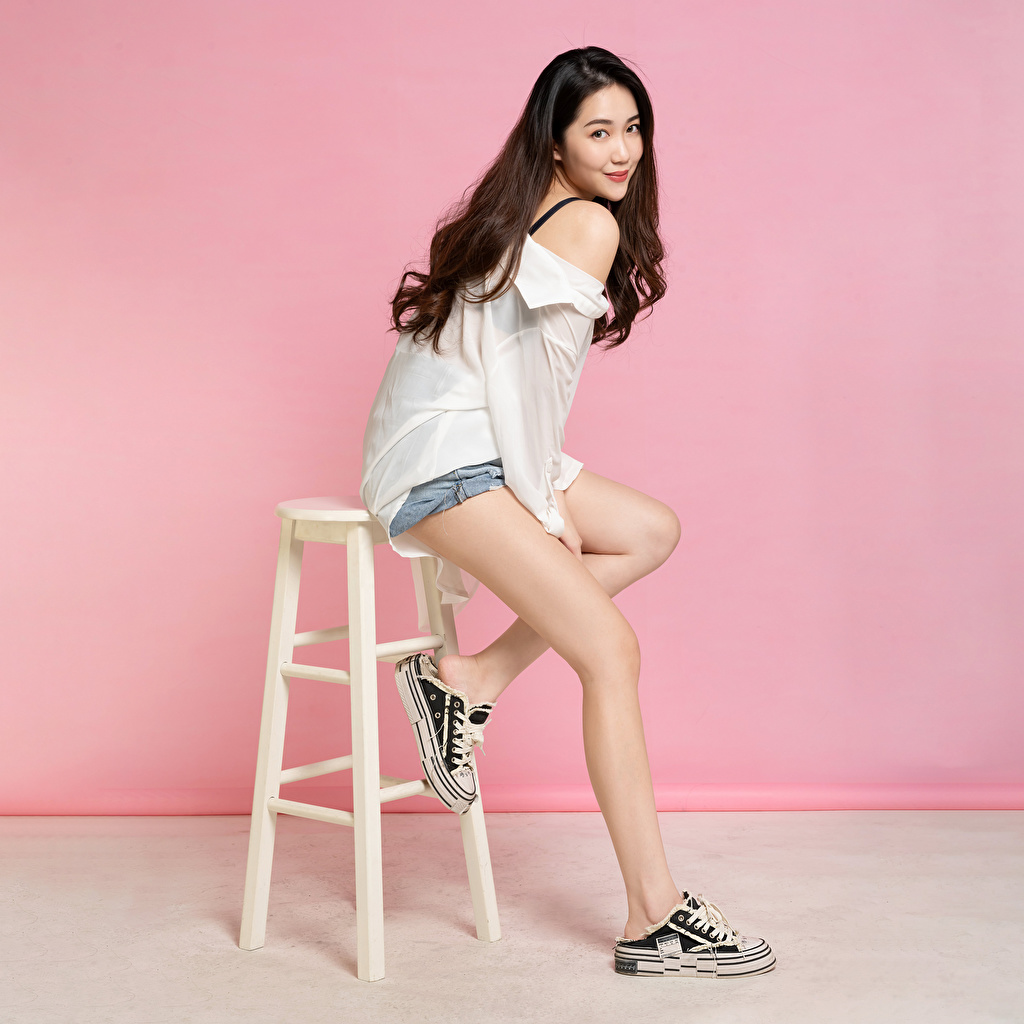 Picture Brown haired posing Blouse young woman Legs Asiatic Chairs Shorts Glance Pose Girls female Asian Chair Staring