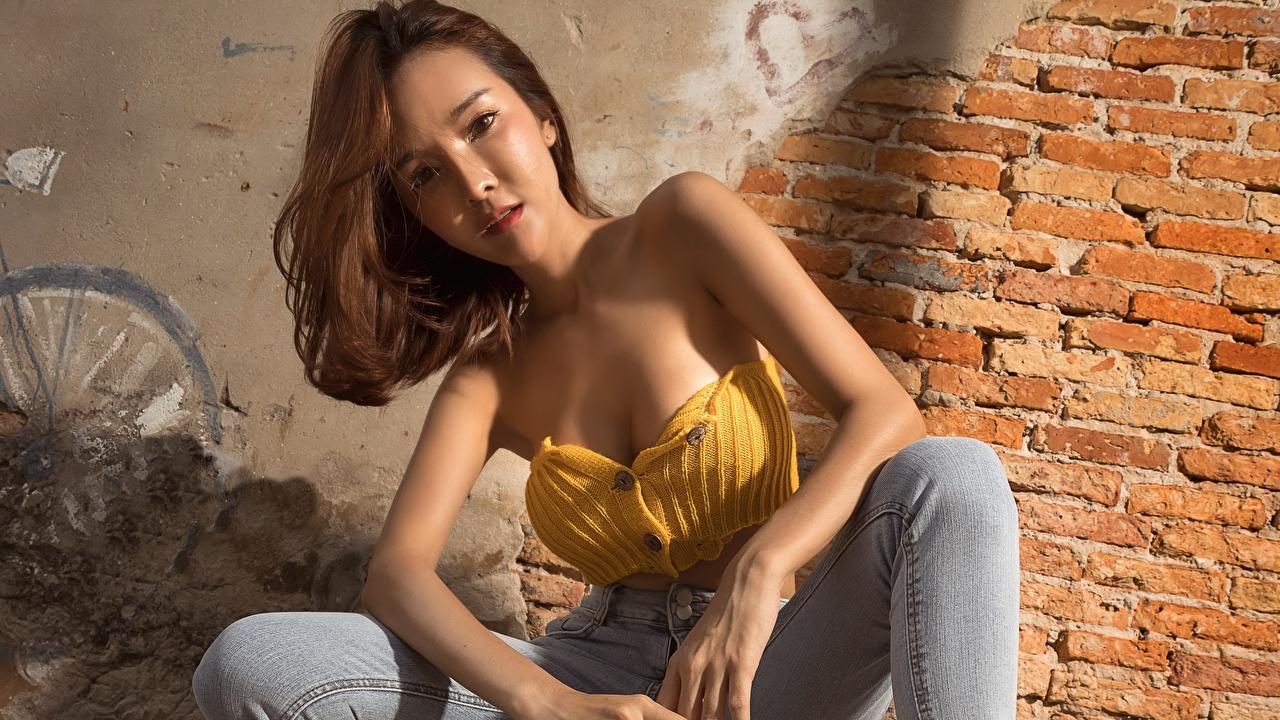 Desktop Hintergrundbilder Braune Haare posiert Mädchens asiatisches aus backsteinen Hand sitzt wände Starren Braunhaarige Pose junge frau junge Frauen Asiaten Aus Ziegel Asiatische wand Mauer sitzen Sitzend Blick