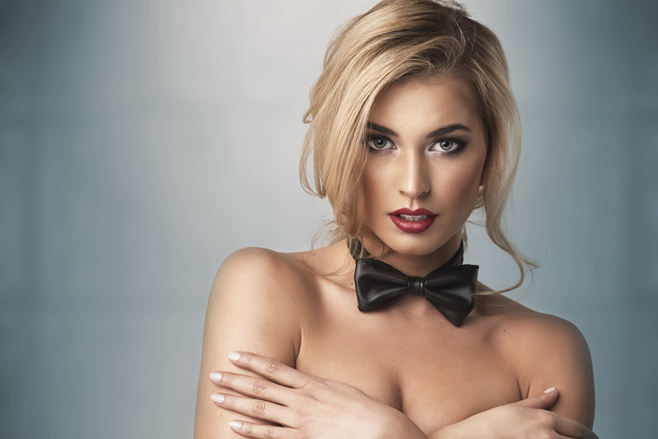 Pictures Blonde girl young woman Fingers Bow tie Gray background Girls female