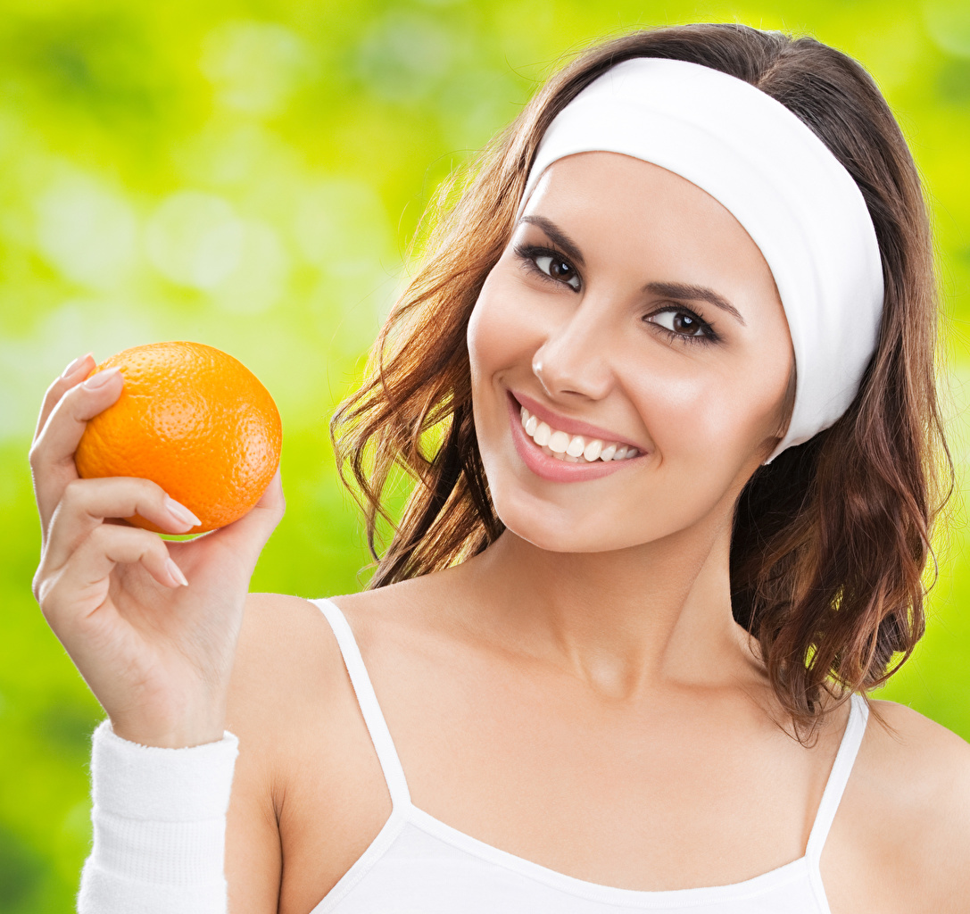 Photo Brown haired Smile Face young woman Orange fruit Hands Glance Girls female Staring