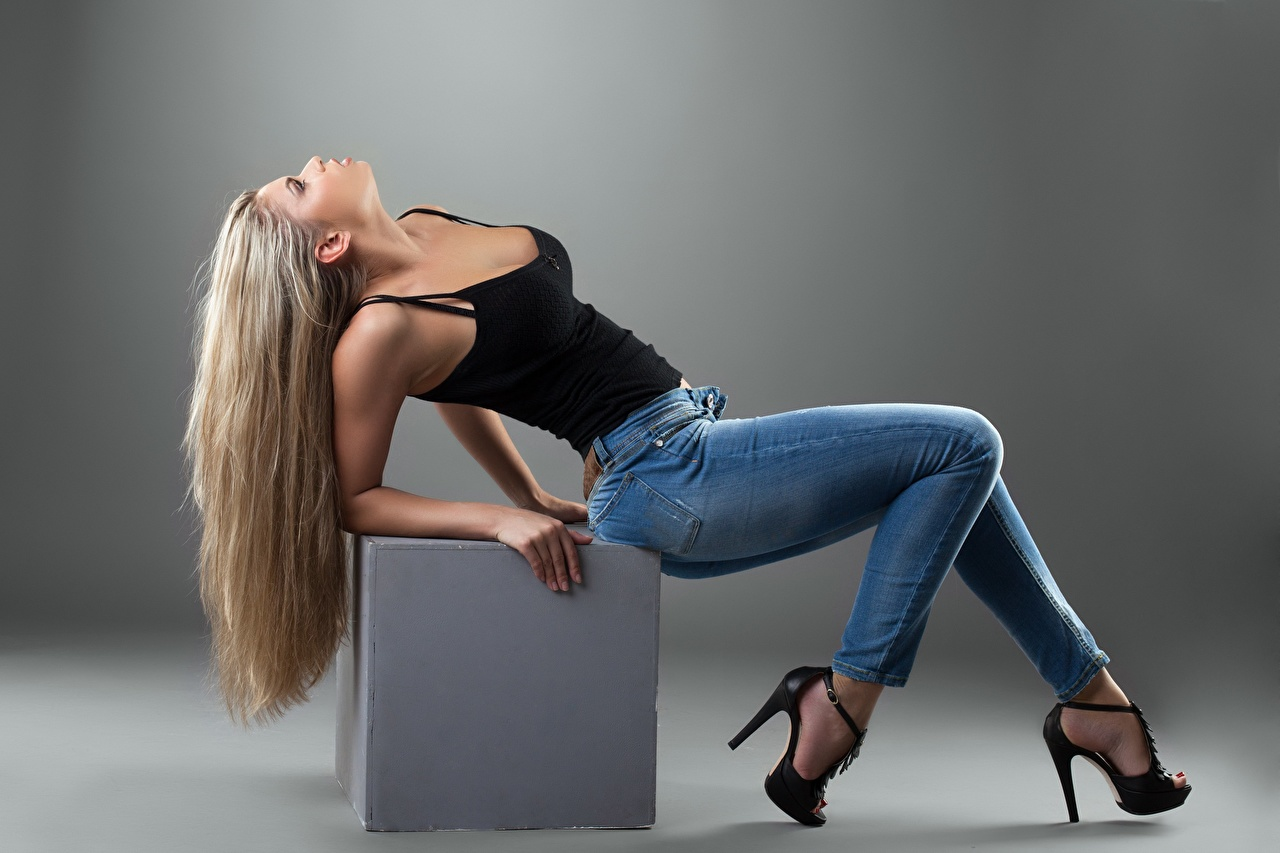 Photos Blonde girl Cube posing female Legs Jeans Gray background Stilettos Pose Girls young woman high heels
