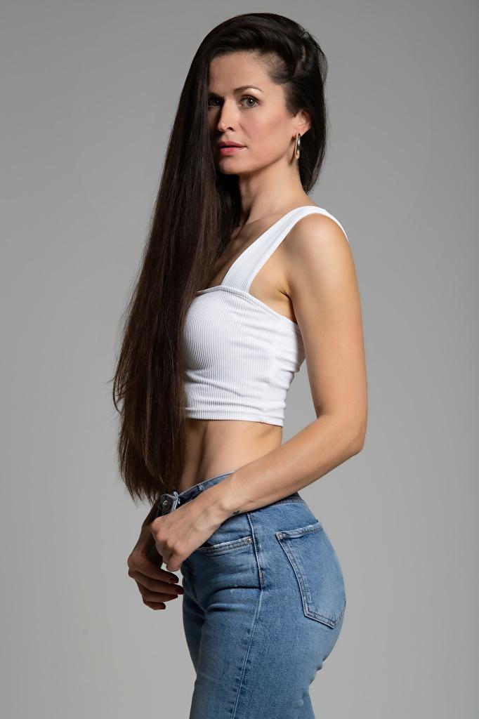 Bilder Brünette Antonija Pose Haar junge frau Unterhemd Hand Starren Grauer Hintergrund  für Handy posiert Mädchens junge Frauen Blick