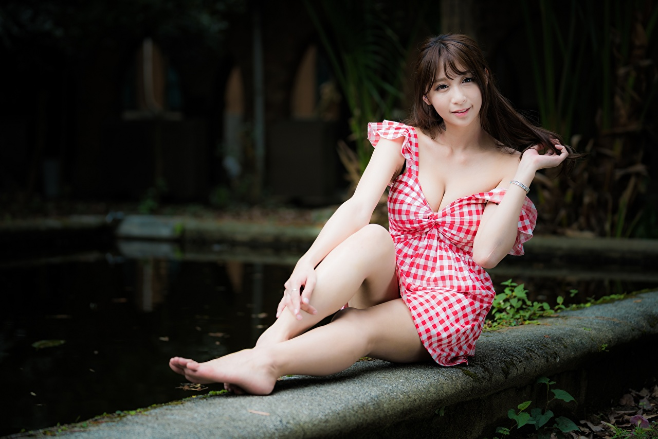 Photo Brown haired Bokeh young woman Legs Asiatic Hands Sitting Dress blurred background Girls female Asian sit gown frock