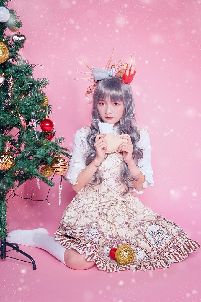 Fotos Neujahr Tannenbaum junge Frauen Asiatische sitzt Kugeln Blick Kleid Farbigen hintergrund  für Handy Mädchens junge frau Christbaum Weihnachtsbaum Asiaten asiatisches sitzen Sitzend Starren