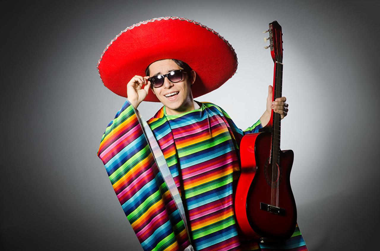 Fotos von Mann Gitarre Lächeln Der Hut Brille Grauer Hintergrund
