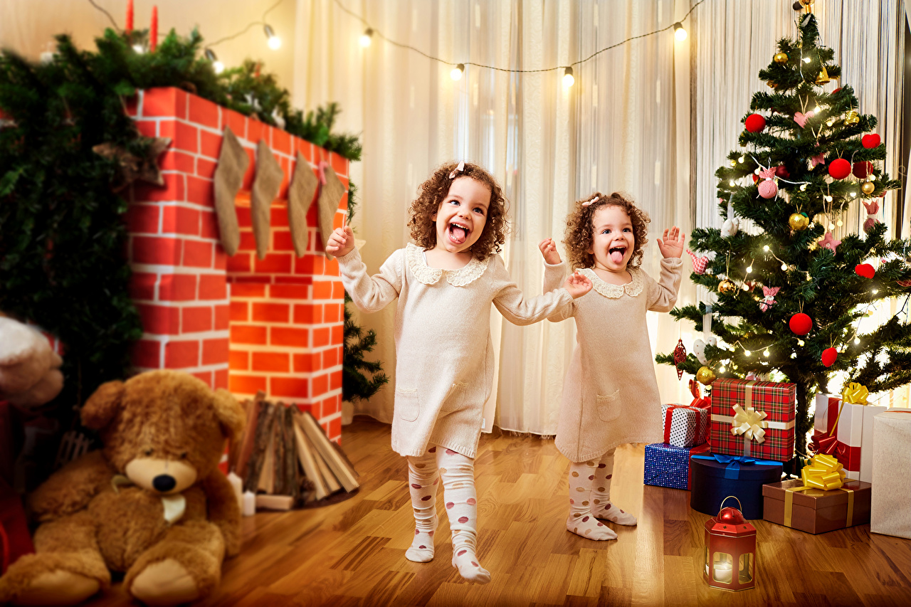 Photos Little girls Christmas happy laughs child Two New Year tree present Fireplace Teddy bear Holidays New year Joy laugh joyful Laughter Children 2 Christmas tree Gifts